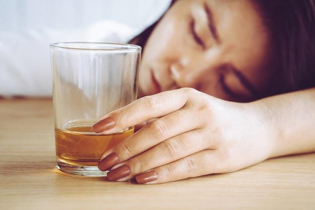 Dronken vrouw hand met een glas alcohol te slapen
