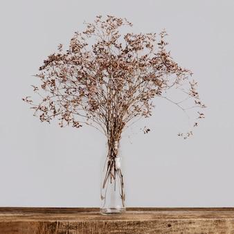 Droog bloemboeket in een glazen fles op een houten tafel op grijs