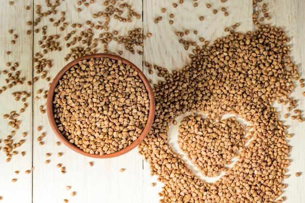 Droog boekweit in bruine kleikom op houten lijst. glutenvrij graan voor een gezond dieet