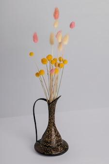 Droog decoratief boeket in een vaas op een grijze muur.