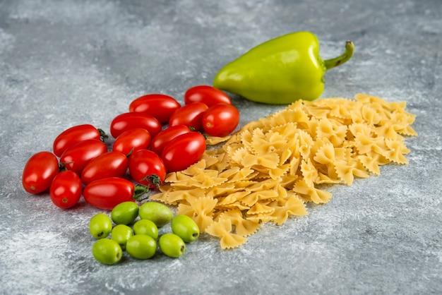 Droog farfalle en groenten op marmer.