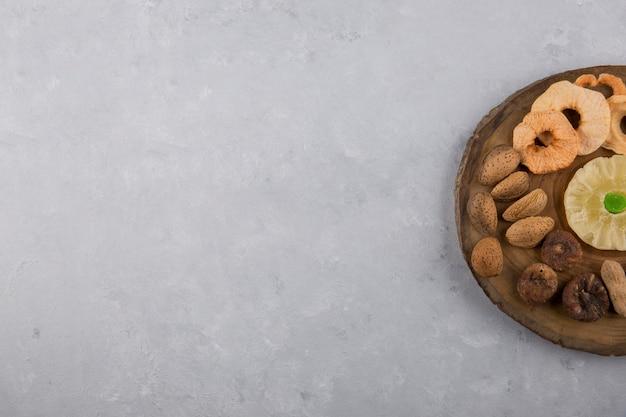 Droog fruit en snacks in houten schotel