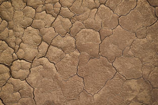 Droog gebarsten aarde tijdens in een regenachtig seizoen omdat het gebrek aan regentekort van water de achtergrond van de grondtextuur barstte