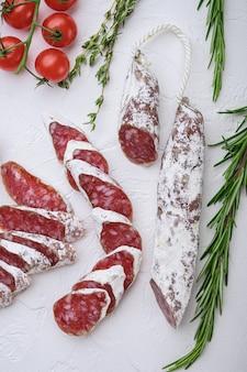 Droog genezen fuet salami worst plakjes met kruiden op wit, topview