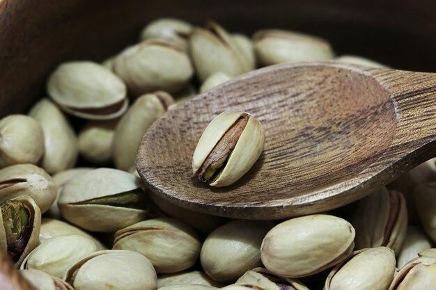 Droog geroosterde pistachenoten in houten lepel