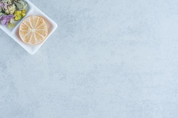 Droog gesneden citroen, theeblaadjes en bloem in de kom op marmer.
