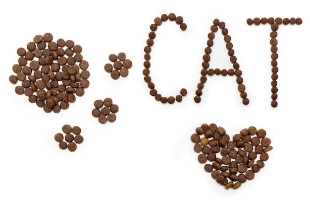 Droog hondenvoer in de vorm van een hart, een kattenpoot en letters cat, geïsoleerd op een witte achtergrond. hartvormig voer voor huisdieren. gezond voedselconcept voor huisdieren.
