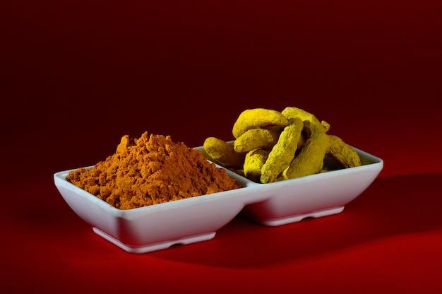 Droog kurkumapoeder en wortels of blaft in een witte plaat