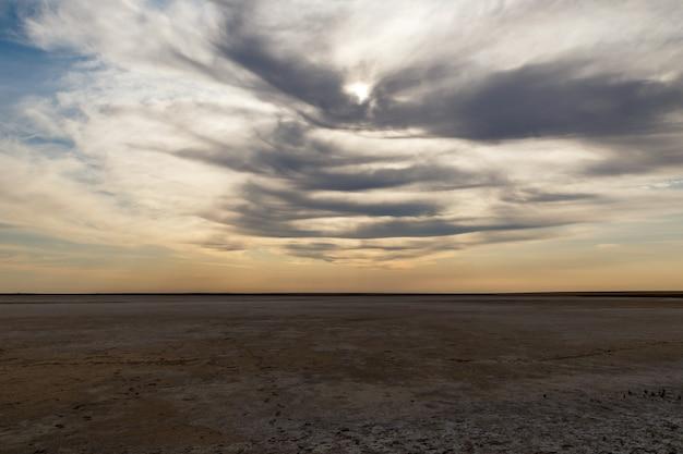 Droog meer, woestijn in kazachstan, zout meer, droog meer in de steppe en bewolkte hemel