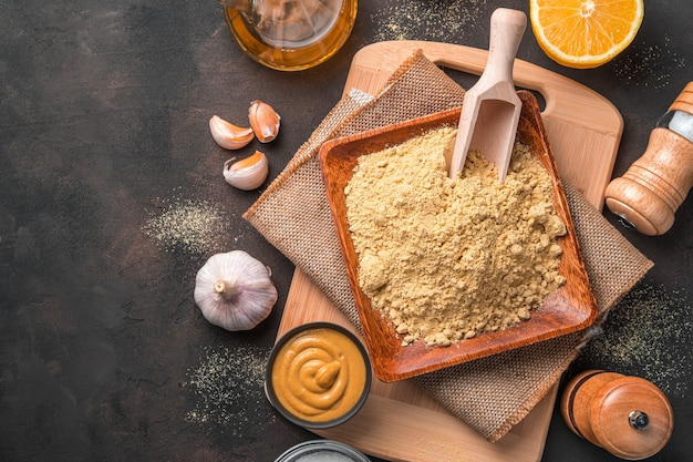 Droog mosterdpoeder en kant-en-klare mosterd op een bruin bureau met ingrediënten