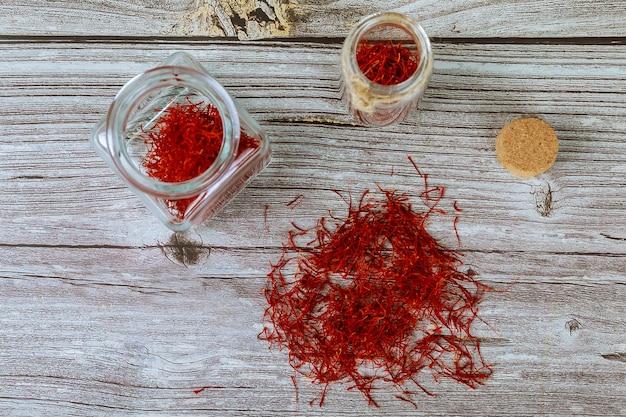 Droog organisch rood saffraankruid in kruik op houten achtergrond