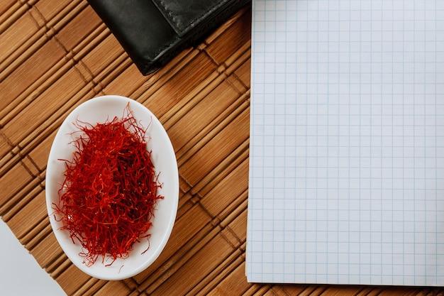 Droog saffraankruid op een witte plaat op houten achtergrond. ruimte kopiëren.
