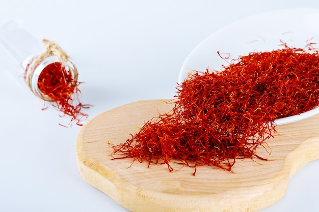 Droog saffraankruid op plaat op witte achtergrond. houten bord. het gebruik van saffraan bij koken, medicijnen, cosmetologie.
