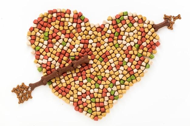 Droog voedsel voor huisdieren in de vorm van een hartvorm die op witte achtergrond wordt geïsoleerd