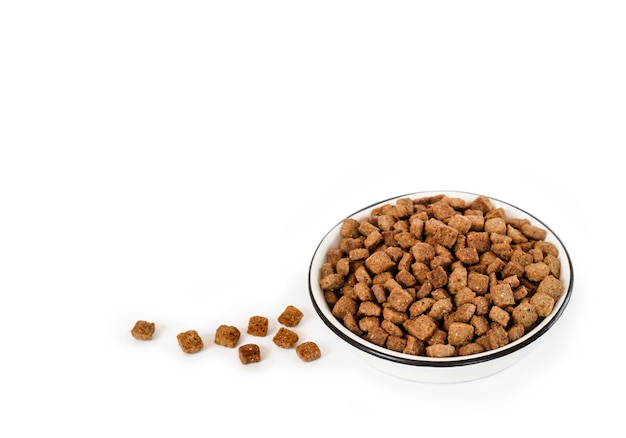 Droog voedsel voor huisdieren in een witte ceramische kom die op witte oppervlakte wordt geïsoleerd