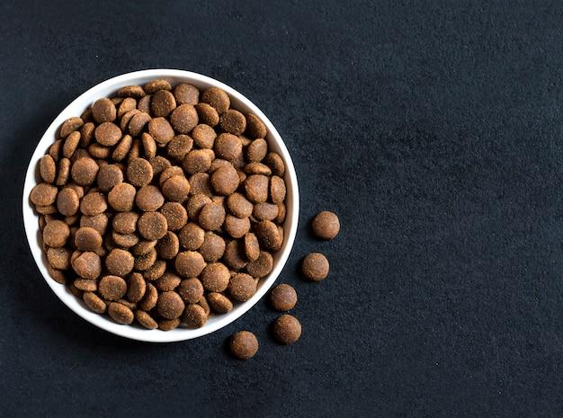 Droog voedsel voor huisdieren in een witte keramische kom op zwart oppervlak. plat, bovenaanzicht