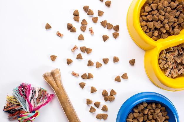 Droog voedsel voor huisdieren in kom en speelgoed voor honden op witte achtergrond bovenaanzicht