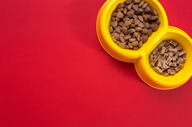 Droog voedsel voor huisdieren in kom op rode achtergrond bovenaanzicht. stilleven. ruimte kopiëren