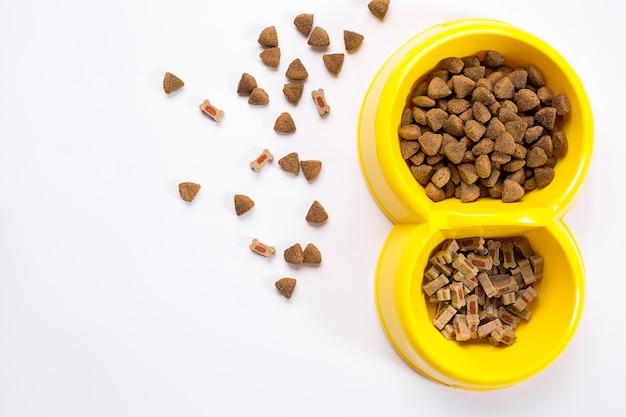 Droog voedsel voor huisdieren in kom op witte achtergrond bovenaanzicht
