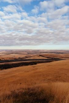 Droog woestijngebied met een weg in het midden en verbazingwekkende wolken in de lucht