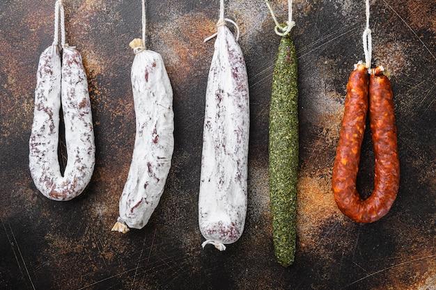 Drooggezouten chorizo en fuet salami-worsten die op oude metalen achtergrond hangen.