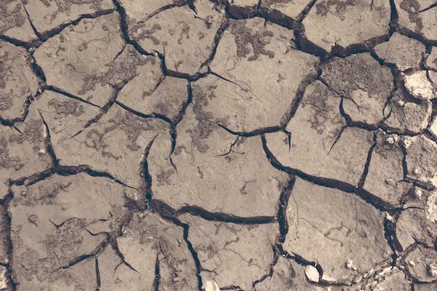 Droogte, de grond barst, geen warm water, gebrek aan vocht. gedroogde en gebarsten grond, gebarsten oppervlak, droge grond in droge gebieden.
