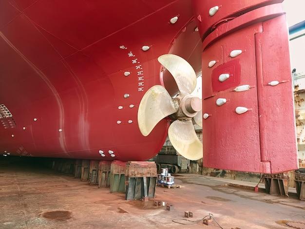 Droogvrachtschip met stuurpropeller ondergaat reparaties in droogdok op de scheepshelling van een scheepswerf