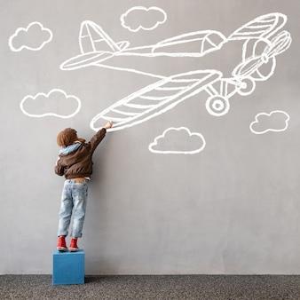 Droom groots! gelukkig kind tekent een krijtvliegtuig op de muur. kinderen verbeelding en reisconcept