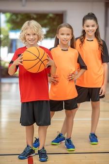 Droom team. kinderen in sportkleding staan met een bal en kijken gelukkig