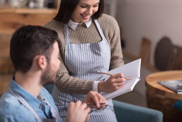 Droom team. mooie schattige jonge vrouw glimlachend en notities tonen aan haar vriend tijdens het schrijven in een notitieblok.