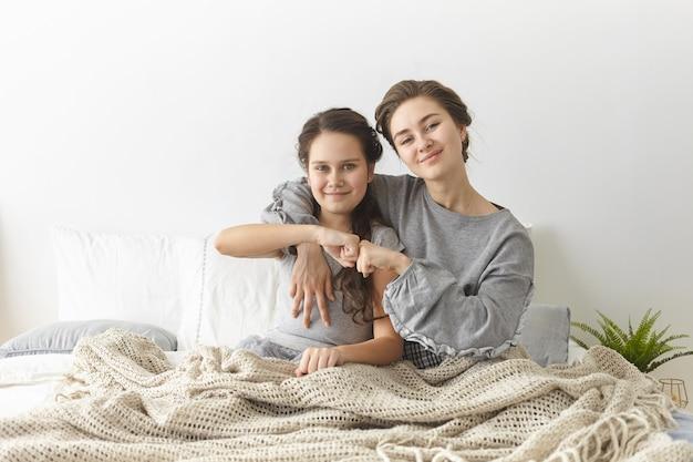 Droom team. schattig schattig meisje zit in de slaapkamer met haar prachtige jonge moeder, vuisten stoten en glimlachend vol vertrouwen naar de camera.