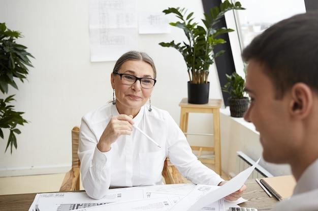 Droomteam, samenwerking en creativiteitsconcept. mooie vrolijke rijpe vrouwelijke architect die witte blouse en glazen draagt die haar getalenteerde ambitieuze jonge mannelijke collega prijst, zijn tekeningen controleert