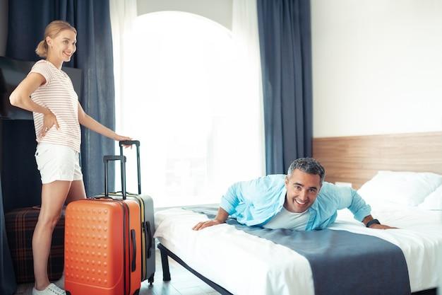 Droomvakantie. glimlachend getrouwd stel is gelukkig eindelijk ontspannen in hun nieuwe hotelkamer.
