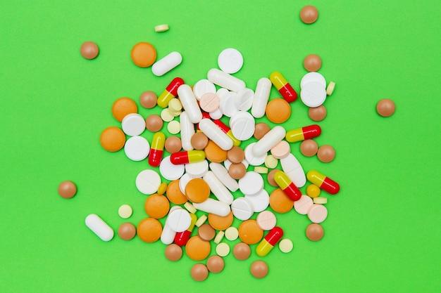 Drugs capsules en pillen op geïsoleerd op groen