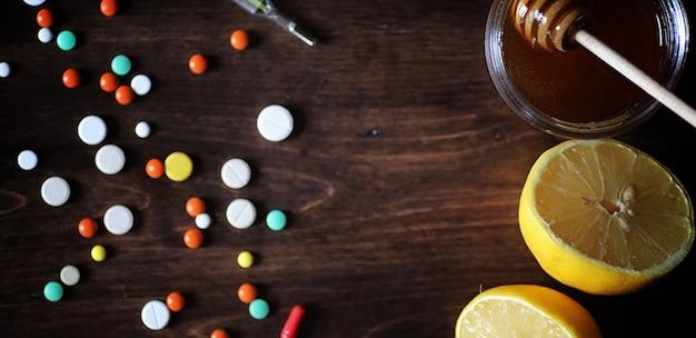 Drugs en pillen op een houten tafel. verschillende middelen om verkoudheid te voorkomen. thee met citroen en honing. glazen beker met thee schijfje citroen en een pot honing.