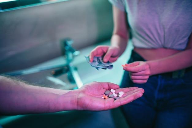 Drugs kopen. drugshandel en verkoop. hand van drugsverslaafde met geld kopen van drugs van drugsdealer in nachtclub. stop drugsgebruik