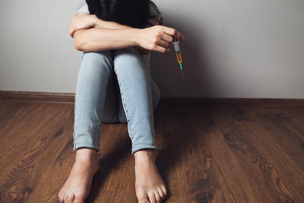 Drugsverslaafde zittend op de vloer met een spuit