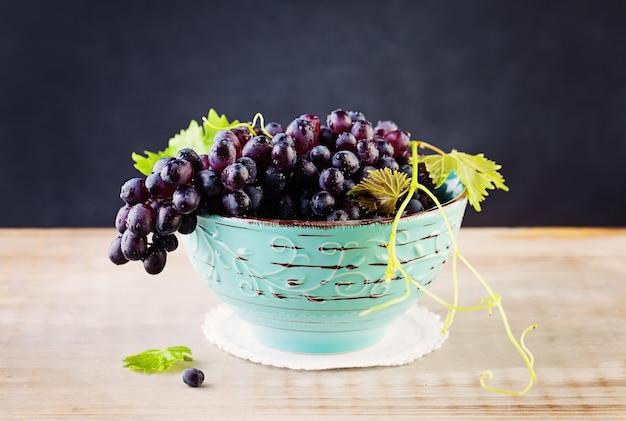 Druif en grapevine met groene bladeren op rustieke houten plank achtergrond