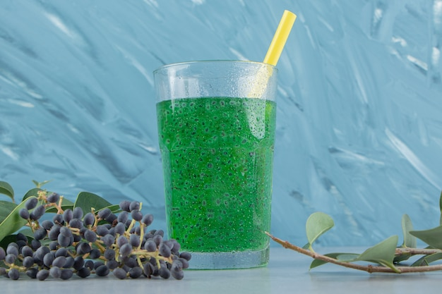 Druif en groen sap op de blauwe achtergrond. hoge kwaliteit foto