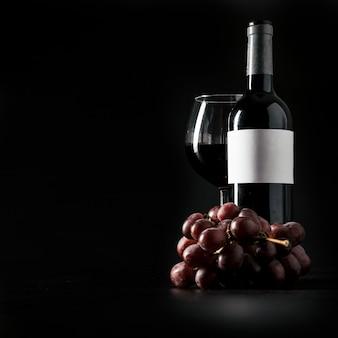 Druif in de buurt van fles en een glas wijn