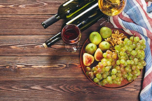 Druif, kaas, vijgen en honing met wijn op houten tafel