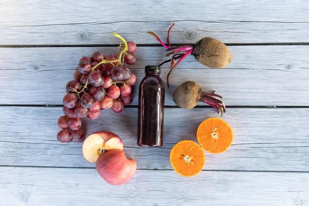 Druif of wijn druif met appelsinaasappel en rode biet koudgeperst tot gezond druivensap in een fles op houten plaat