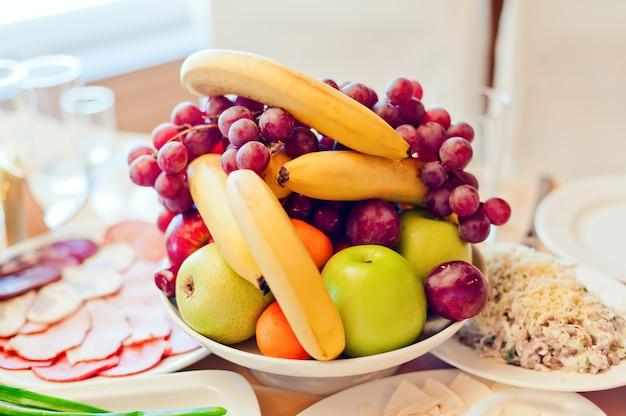 Druiven, appels, peren, bananen en ander fruit in een vaas op een feestelijke tafel.