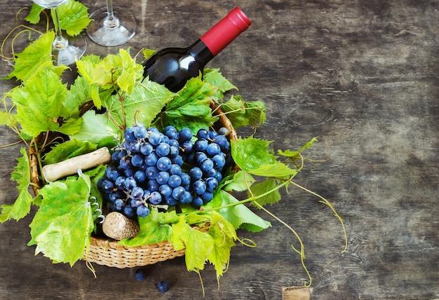 Druiven, een fles wijn, kurken en kurketrekker op een houten oude tafel, rustieke stijl