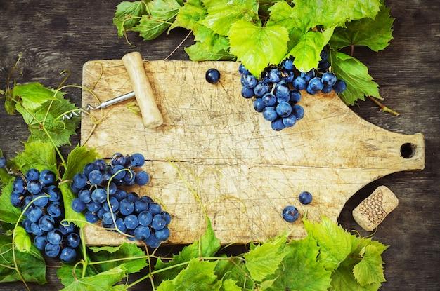 Druiven en oud bord op een houten achtergrond