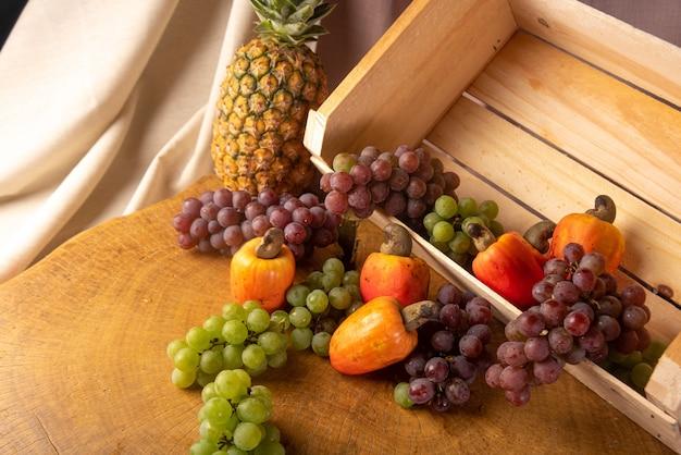 Druiven in een houten kist en cashewnoten en ananas met stoffen op de achtergrond en rustiek hout, lage scherptediepte