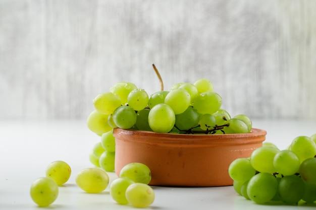 Druiven in een kleiplaat op witte oppervlakte, zijaanzicht.