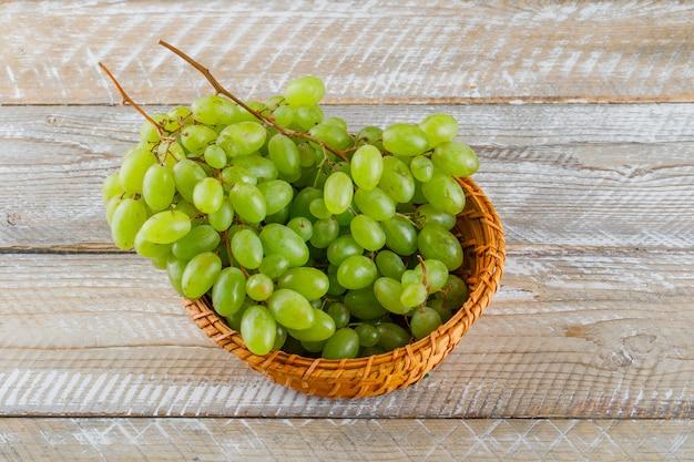 Druiven in een rieten mand op een houten achtergrond. hoge kijkhoek.