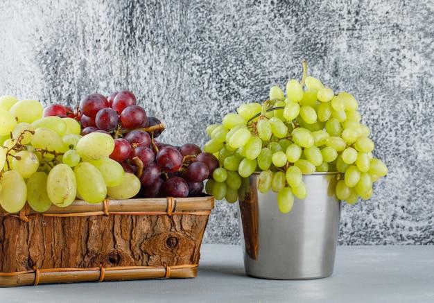 Druiven in mini-emmer en mand zijaanzicht op gips en grungy grijs