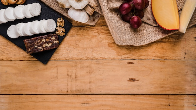Druiven; knoflook en verschillende kazen op jutetextiel over houten plank
